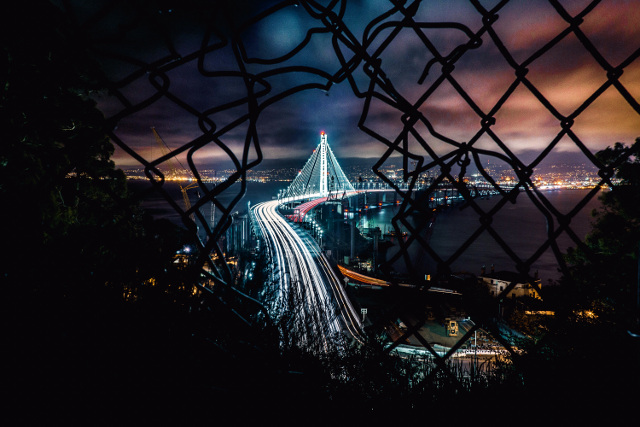 night-time cityscape through broken wire fence