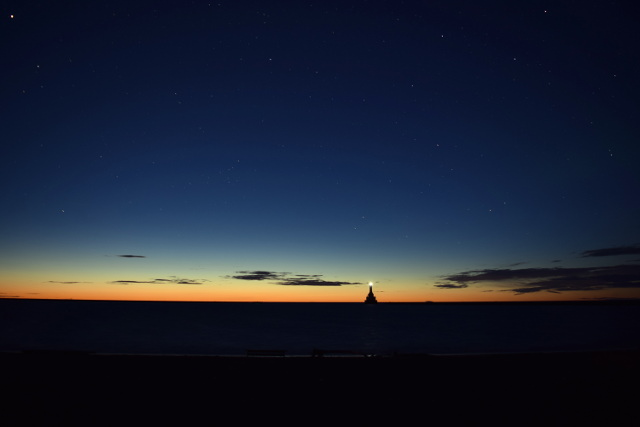 small beacon on sea horizon at last light
